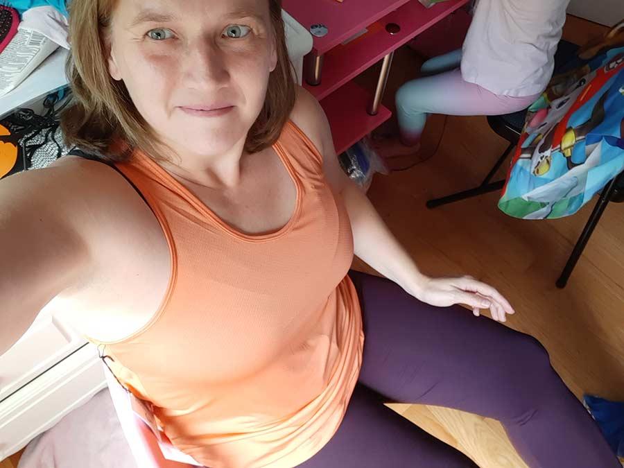 susan wearing zyia orange tank top and zyia purple leggings